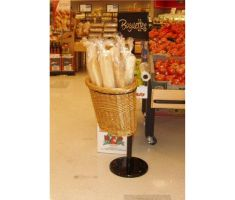 Single willow basket display in store, filled with baguettes