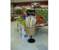 Single willow basket stand filled with baguettes, next to produce