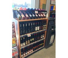 Wine topper sitting atop a wine display holding wine bottles