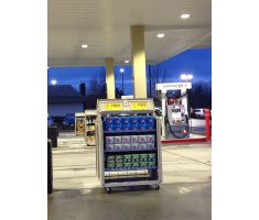 Mobile Cart at gas station open outside at gas station holding cartons of soda. Mobile cart has 3 adjustable shelves and casters.