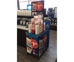 Floor display with wire holders for cups and lids. Lids and cups can be grabbed from the top, but more can be stored inside of the display as not all holders are totally visible. There is also a top mounted sign frame that rises way above the lid and cup storage. This picture shows the display inside a gas station.
