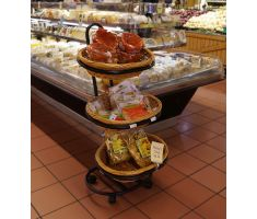Three tier oval basket display filled with chips and tortillas in front of cheese cooler