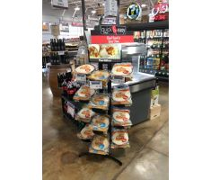 4 Tier stand with 3 rings per tier holding whole wheat and flour tortillas next to a deli case, in front of a beer cooler