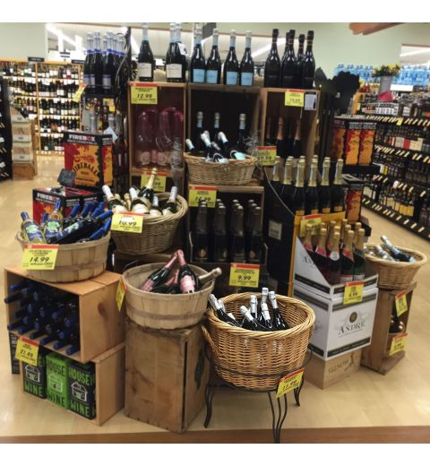 Medium willow basket filled with wine bottles in front of wine display